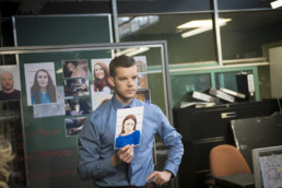 Russell Tovey as DS Huw Brydon holds a photograph of a suspect in Talking To The Dead