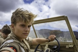 Tom Glynn-Carney as Lance Corporal Tony Armstrong driving a Land Rover through Aden in Amazon The Last Post